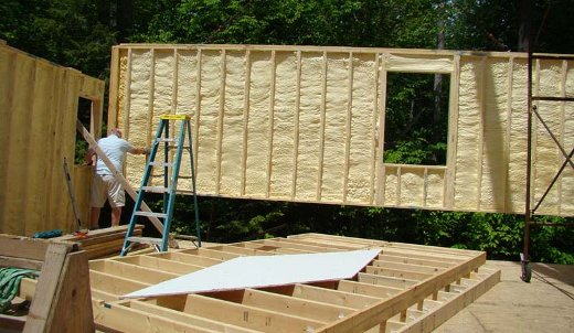 A panelized home wall being placed. Note this is an open wall system with